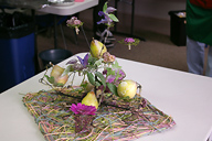 An arrangement for a table with waxed fruits and flowers